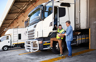 Buy stock photo Shot of two coworkers talking together next to a large truck outside of a distribution center