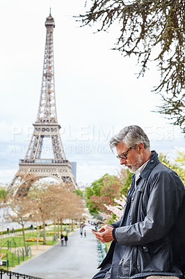 Buy stock photo Shot of a handsome mature man using a cellphone in Paris with the Eiffel Tower in the backgournd