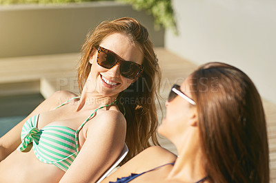 Buy stock photo Shot of two young friends in bikinis talking together while suntanning by a swimming pool