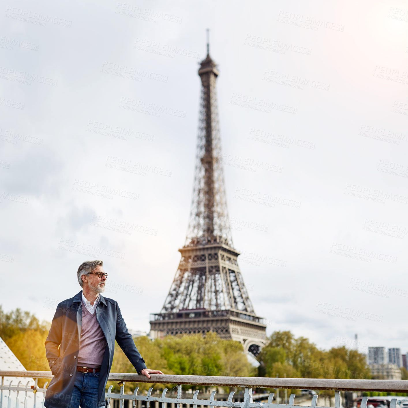 Buy stock photo Shot of a handsome mature man leaning on a railing in Paris with the Eiffel Tower in the backgournd
