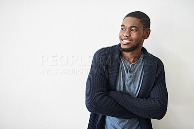 Buy stock photo Studio shot of a smiling young man standing with his arms crossed against a gray background