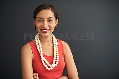 Buy stock photo Studio portrait of a smiling young woman standing with her arms crossed against a gray background