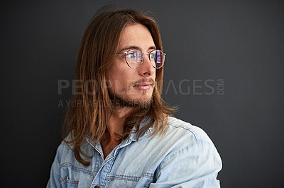 Buy stock photo Studio shot of a young man looking deep in thought against a gray background