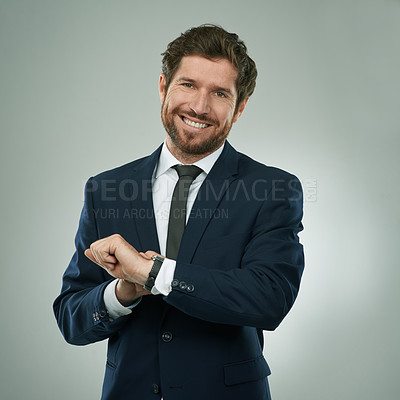 Buy stock photo Studio portrait of a corporate businessman checking the time against a grey background