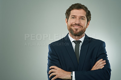 Buy stock photo Studio portrait of a corporate businessman standing with his arms folded against a grey background