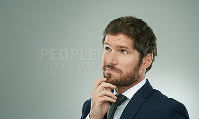 Buy stock photo Studio shot of a thoughtful businessman standing with his hand on his chin against a grey background