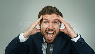 Buy stock photo Studio portrait of a stressed out businessman shouting with his hands on his head against a grey background