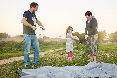 Buy stock photo Cropped shot of a young family putting up a tent together