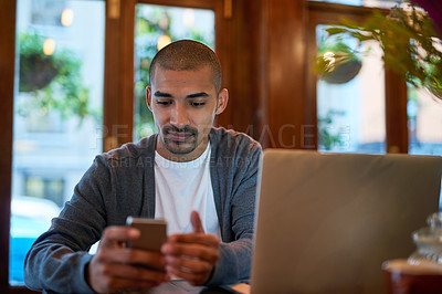 Buy stock photo Cropped shot of a young man texting on his cellphone in a coffee shop
