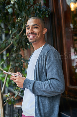 Buy stock photo Portrait of a young man texting on his cellphone outside