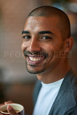 Buy stock photo Portrait of a young man enjoying a cup of coffee in a cafe