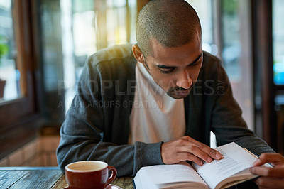 Buy stock photo Cropped shot of a young man reading a book in a cafe