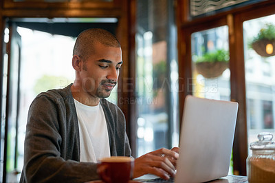 Buy stock photo Cropped shot of a young man working on his laptop in a cafe