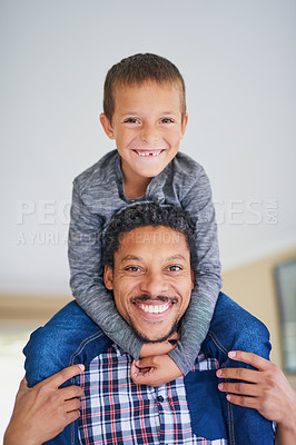 Buy stock photo Portrait of a father carrying his son on his shoulders at home