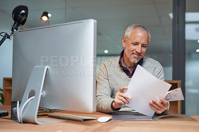 Buy stock photo Portrait of a smiling mature businessman reading paperwork while sitting at his desk in an office