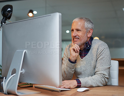 Buy stock photo Shot of a smiling mature businessman working on a computer in an office
