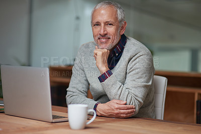 Buy stock photo Portrait of a smiling mature businessman using a laptop while working in an office