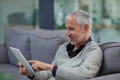 Buy stock photo Shot of a mature businessman using a digital tablet while sitting on a sofa in an office
