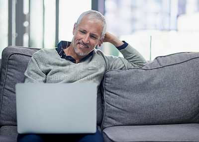 Buy stock photo Shot of a mature businessman using a laptop while sitting on a sofa in an office