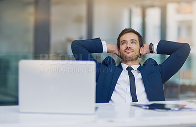 Buy stock photo Shot of a young businessman looking relaxed with his hands behind his head
