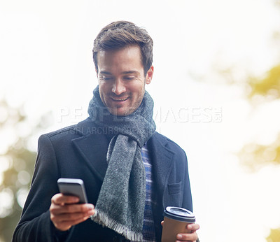 Buy stock photo Shot of a young man using his phone outside