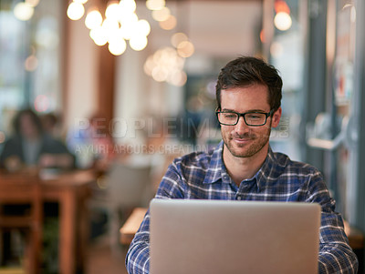 Buy stock photo Shot of a young man using his laptop while sitting in a coffee shop