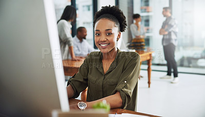 Buy stock photo Portrait of a young businesswoman working on a computer in a modern office with colleagues in the background
