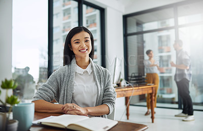 Buy stock photo Portrait of a young businesswoman sitting at her desk with colleagues in the background