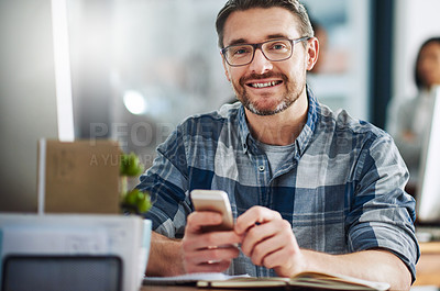 Buy stock photo Portrait of a mature businessman texting on a cellphone in an office