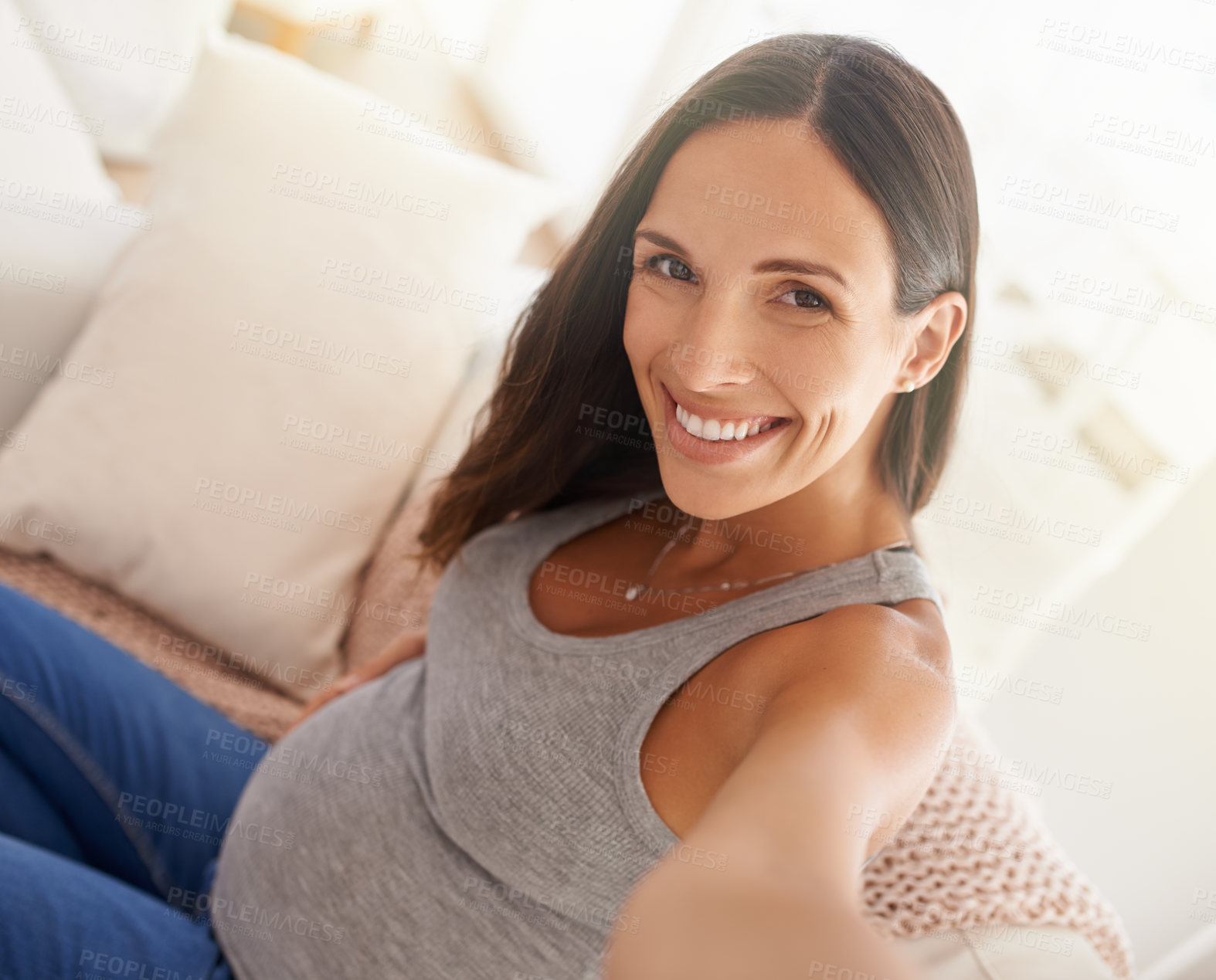 Buy stock photo Shot of a pregnant woman taking a selfie while relaxing at home