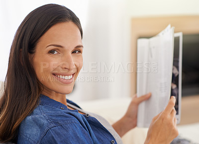 Buy stock photo Shot of a young woman relaxing at home with a magazine