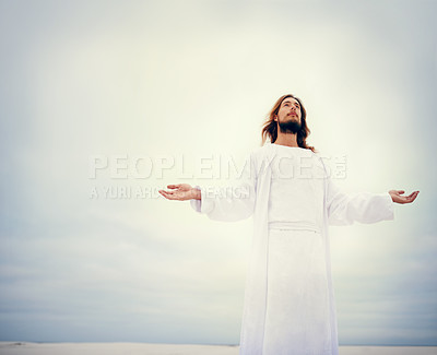 Buy stock photo Shot of Jesus standing with his arms outstretched on a bare landscape