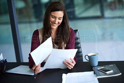 Buy stock photo Shot of a young businesswoman working on her admin