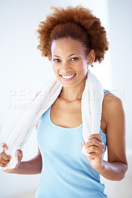 Buy stock photo Potrait of a happy young woman holding a towel around her neck after exercising