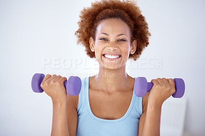 Buy stock photo Portrait of a smiling young woman working out with dumbells in hands at gym