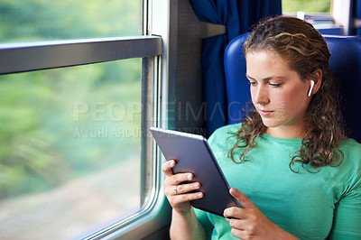 Buy stock photo Shot of a young woman using wireless earphones and a digital tablet on a train