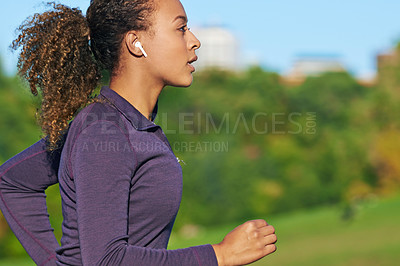 Buy stock photo Shot of a fit young woman using wireless earphones during her workout outside