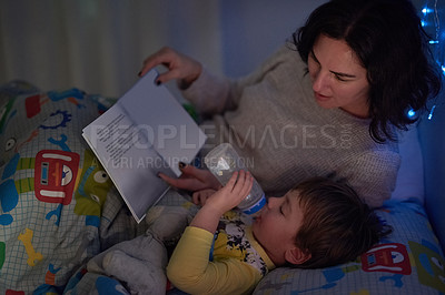 Buy stock photo Cropped shot of a little boy lying in bed while his mom reads a bedtime story