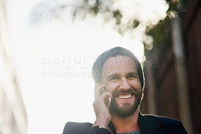 Buy stock photo Cropped shot of a young man talking on a cellphone outside