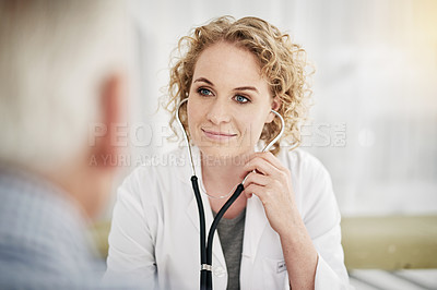 Buy stock photo Shot of a doctor using a stethoscope while talking with a senior patient in her office
