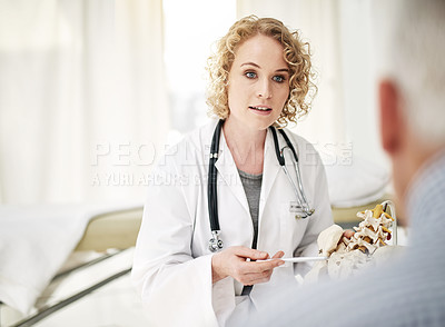 Buy stock photo Shot of a doctor explaining a medical procedure with a model to a senior patient while sitting in her office