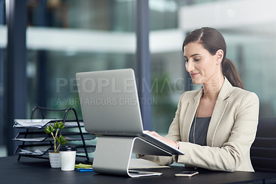 Buy stock photo Shot of a professional businesswoman using a laptop at her office desk