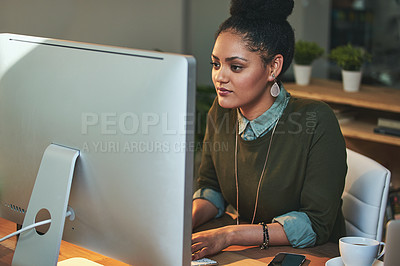 Buy stock photo Shot of an attractive young woman working on her computer in the office