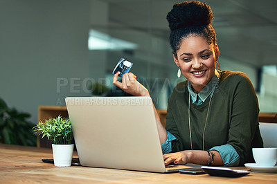 Buy stock photo Shot of an attractive young woman shopping online while working in the office