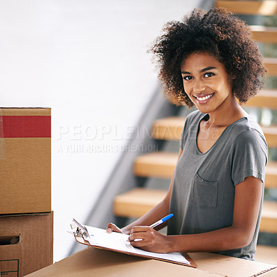 Buy stock photo Shot of a young woman checking her clipboard while busy packing up