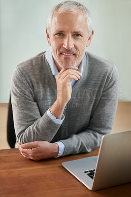 Buy stock photo Portrait of a mature businessman looking thoughtful while working on his laptop in the office