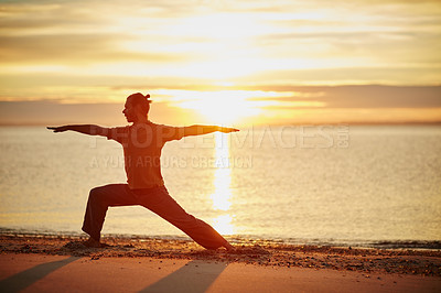 Buy stock photo Shot of a man practicing the warrior pose during his yoga routine at the beach