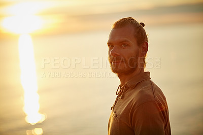 Buy stock photo Portrait of a man relaxing at the beach during sunset