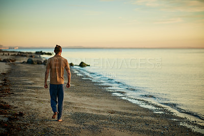 Buy stock photo Rearview shot of a man going for a walk along the water's edge at the beach