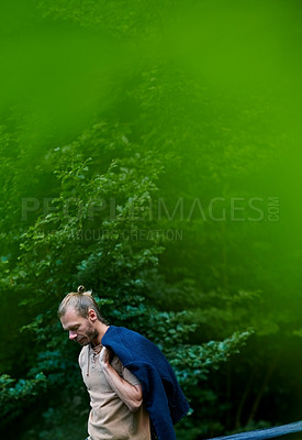 Buy stock photo Shot of a handsome man walking outdoors